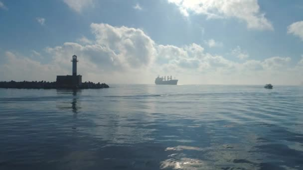 Schöner Morgen über den glitzernden Wellen des Meeres. Leuchtturm und Segelboot, Blick zum Horizont.