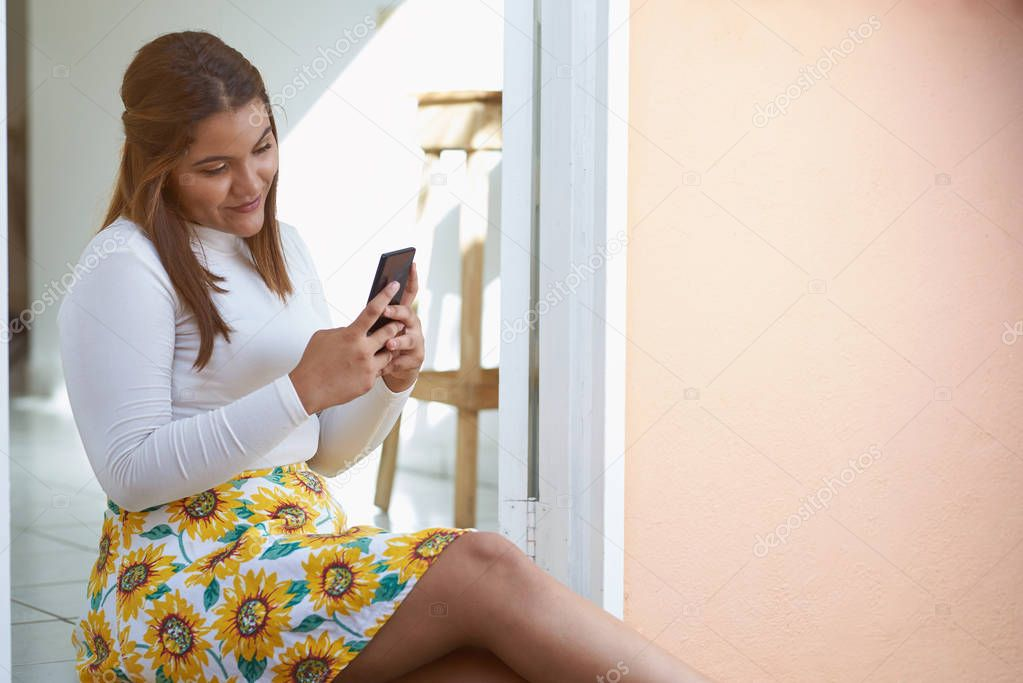 Young woman with smartphone sit in house