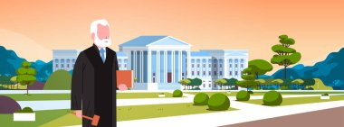 judge man court worker in judicial robe holding book and hummer standing in front of courthouse exterior landscape background horizontal portrait