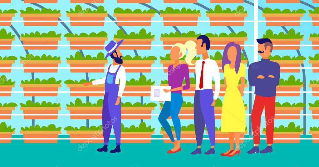 farmer in uniform with agriculture engineers group inspecting growing plants vertical farm organic hydroponic vegetables modern greenhouse interior horizontal full length