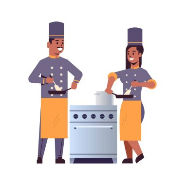 cooks couple professional chefs using frying pan stirring food african american man woman restaurant kitchen workers in uniform standing together near stove cooking concept flat full length