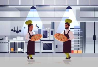 professional chefs couple holding trays with fresh pizza african american man woman in uniform standing together cooking food concept modern restaurant kitchen interior horizontal full length