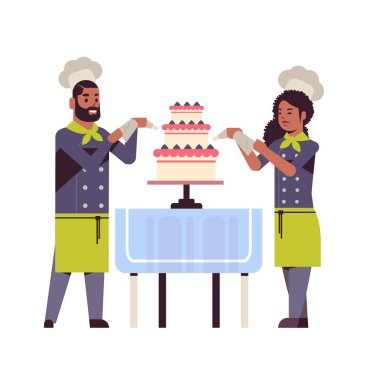 cooks couple professional pastry chefs decorating tasty wedding cream cake african american woman man restaurant workers in uniform cooking food concept flat full length
