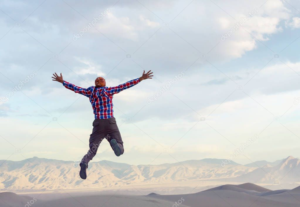 Jumping boy high in mountains