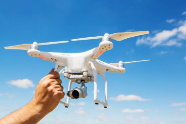 Quadcopter drone flying against sky