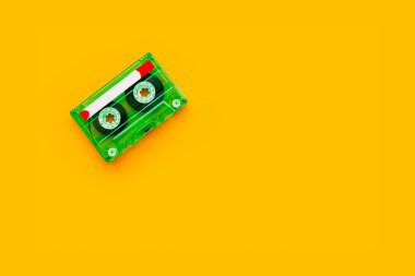 Top view of audio cassette on bright yellow background with copy space, minimalistic composition