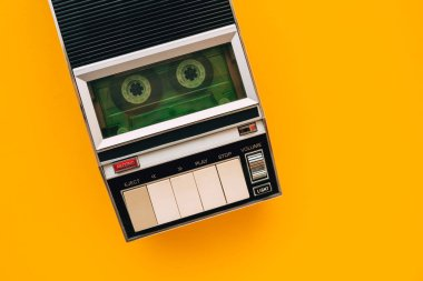 Top view of audio cassette tape player on bright yellow background with copy space, minimalistic retro style composition
