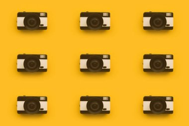 Seamless pattern background of retro hipster photographic camera on yellow backdrop, minimalistic retro style composition stock vector