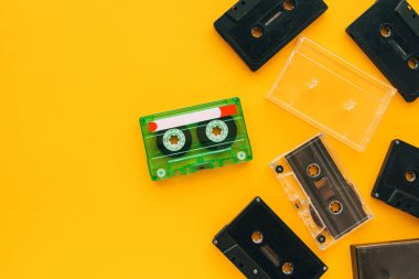 Top view of audio cassettes on bright yellow background with copy space, minimalistic composition