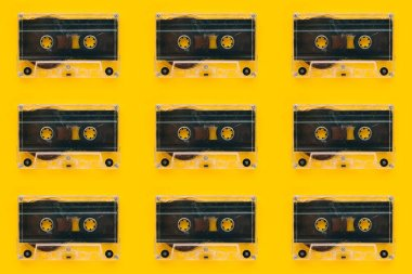 Seamless pattern background of audio cassettes on bright yellow backdrop, minimalistic retro style top view composition