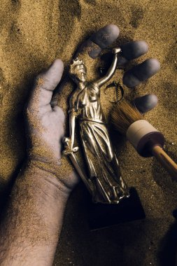 Forensic expert discovering dead body buried in desert sand with Justice statue in hand. Conceptual image for police investigation of an cold case murder crime scene.