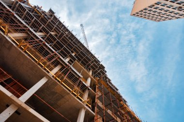 Building construction site with scaffolding, low angle view