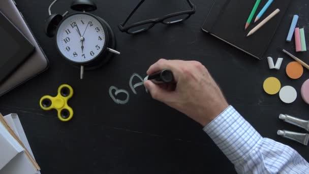 Ruka dospělého muže učitel zapisuje zpět do školy textu na tabuli
