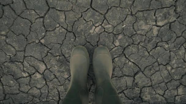 Landwirt in Latex Stiefel stehen auf trockenem Boden Boden, globale Erwärmung und den Klimawandel Änderung Auswirkungen auf Pflanzen wachsen und Ertrag