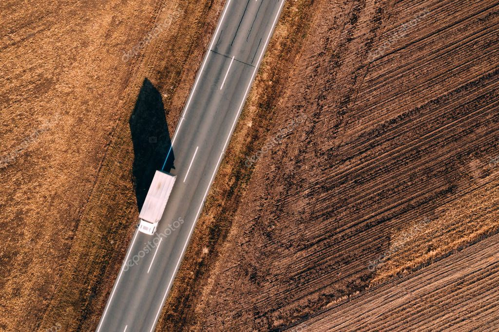 Aerial view of truck on the road through plain countryside from drone pov