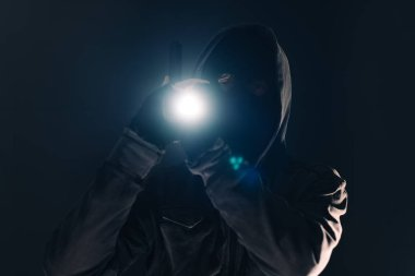 Armed burglar intruder with flashlight torch at night, low key selective focus