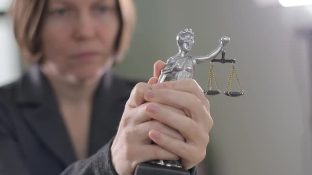 State attorney holding statue of Justice in office, selective focus