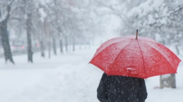Woman with red umbrella in snow enjoying the first snowfall of the winter season