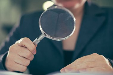 Business corruption audit inspection concept, female inspector using magnifying glass
