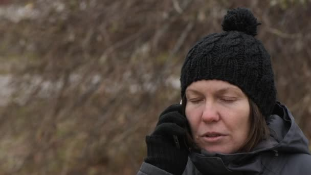 Serious woman talking on mobile phone outdoors on cold winter day