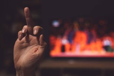 Middle finger at TV, woman showing obscene hand gesture as form of reaction to television show