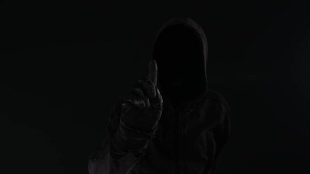 Cyberterror-Konzept mit gesichtsloser männlicher Person mit Kapuze, unauffälligem Filmmaterial mit digitalem Glitch-Effekt