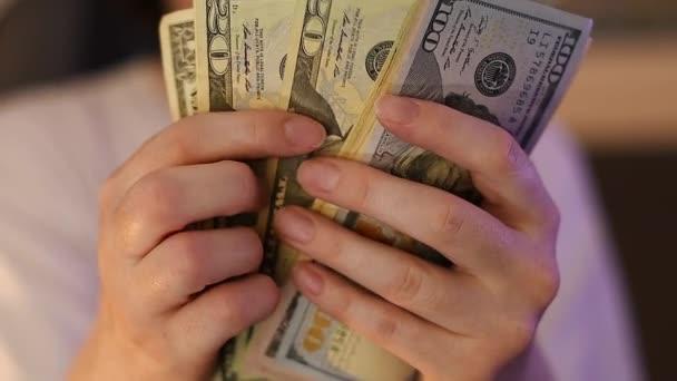 Příležitostné žena počítá americké dolarové bankovky, zblízka z rukou s penězi