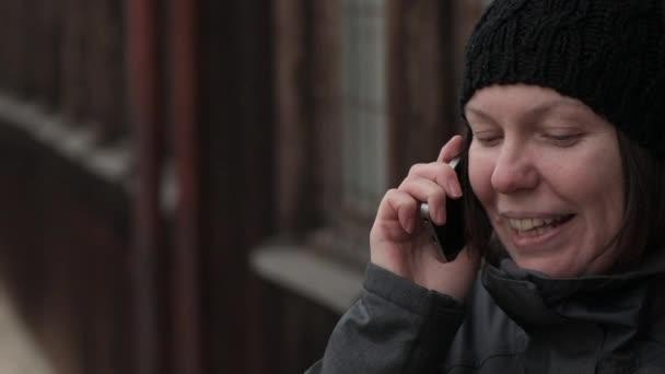 Mobilní telefonní rozhovor, spokojený úsměv dospělý Kavkazský žena mluvila na smartphone ven na ulici na chladné zimní den