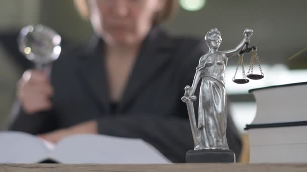 Attorney woman using magnifying glass for law book reading at her office desk, selective focus