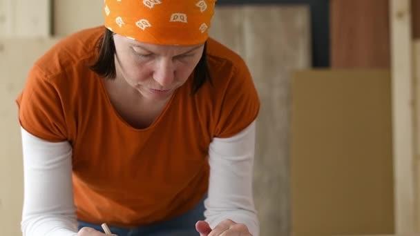 Ženské carpenter s hlavy šátek dělá finanční kalkulace v dílně tesařství ze dřeva