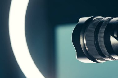 Camera lens and LED ring light in studio, photo and video production conceptual copy space