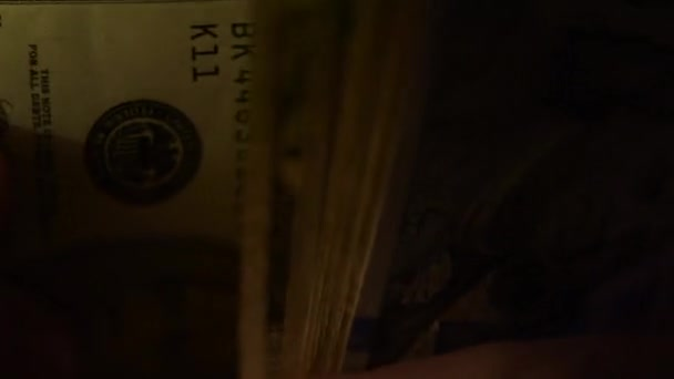 Close up of male hands counting money, US dollar banknotes in dark room