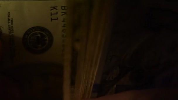 Detailní záběr z mužských rukou počítání peněz, nás dolarové bankovky v temné místnosti