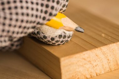Carpenter marking pine wood plank for cutting in woodwork workshop, extreme close up of hand with pencil