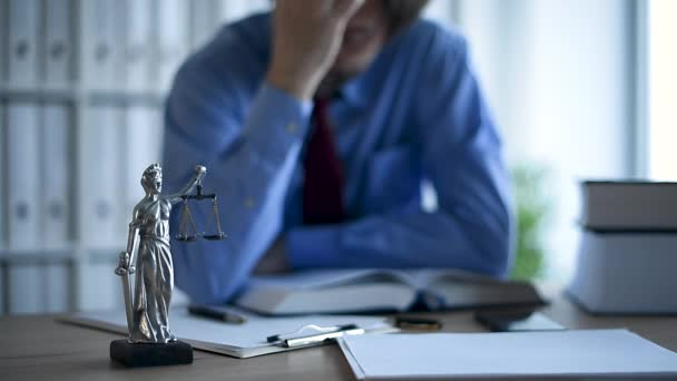 Attorney reading book in law office, selective focus on statue of Lady Justice