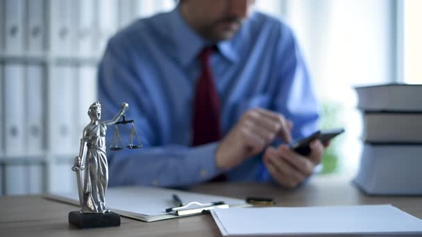 Attorney texting on mobile device and writing notes in law office, selective focus on statue of Lady Justice