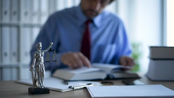 Attorney reading book and writing notes in law office, selective focus on statue of Lady Justice