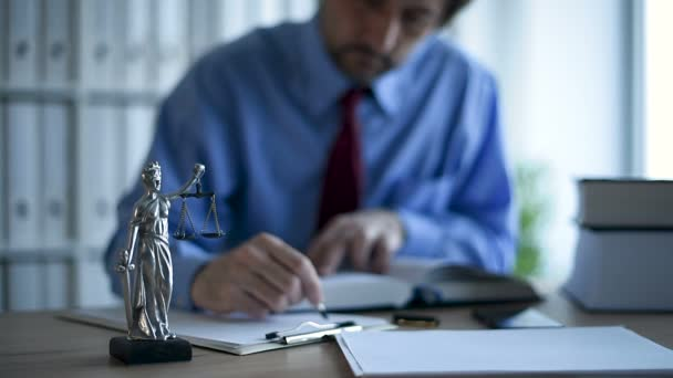 Lawyer writing notes on clipboard note paper in law office, selective focus on statue of Lady Justice