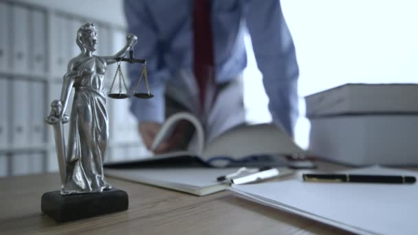 Attorney reading book, flipping pages in law office, selective focus on statue of Lady Justice