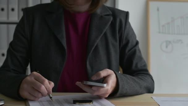 Businesswoman analyzing business data spreadsheet in office, dolly slider shot