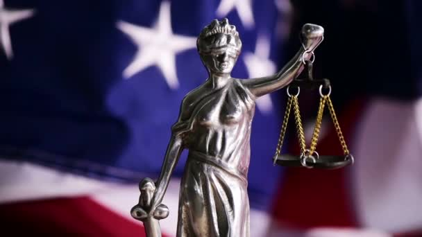 Law and Justice in United States of America, statue of Lady Justice with USA flag in background, dolly slider shot
