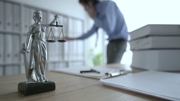 Lawyer talking on mobile phone in law office, selective focus on statue of Lady Justice