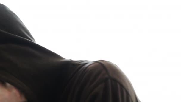 Nervózní muž s kapucí mluvit na mobilním telefonu, izolované na bílém pozadí