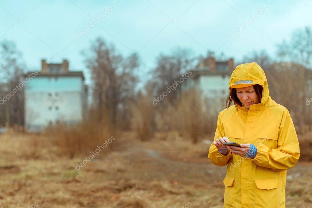 Woman in yellow raincoat texting on mobile phone outdoors