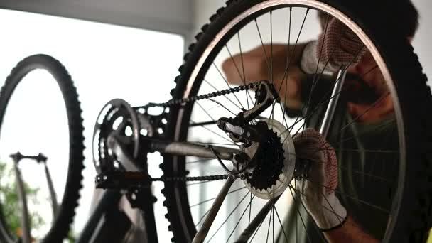 Automechanik opravování starého horského kola v dílně, selektivní záběr