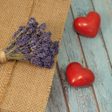 Two ceramic hearts, lavender and burlap on worn blue wooden planks background