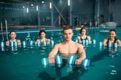 Trenér a skupina ženských aqua aerobik, cvičení s činkami na výcvik v bazénu. Fitness cvičení, vodní sport