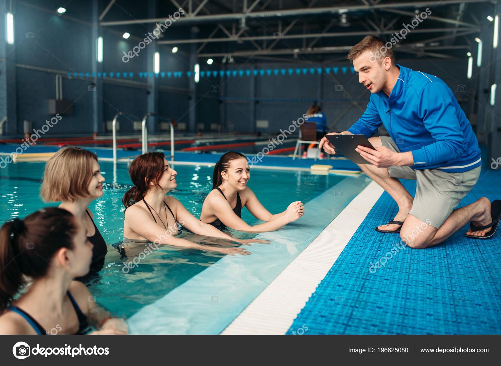 female fitness class male trainer clipboard aqua aerobics swimming