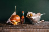 Photo fresh grilled burger, fries and sauce on wooden table, closeup, American fast food