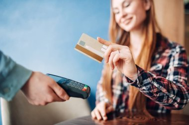 young woman paying with credit card in cafe, waiter's hand with terminal, modern payment technology
